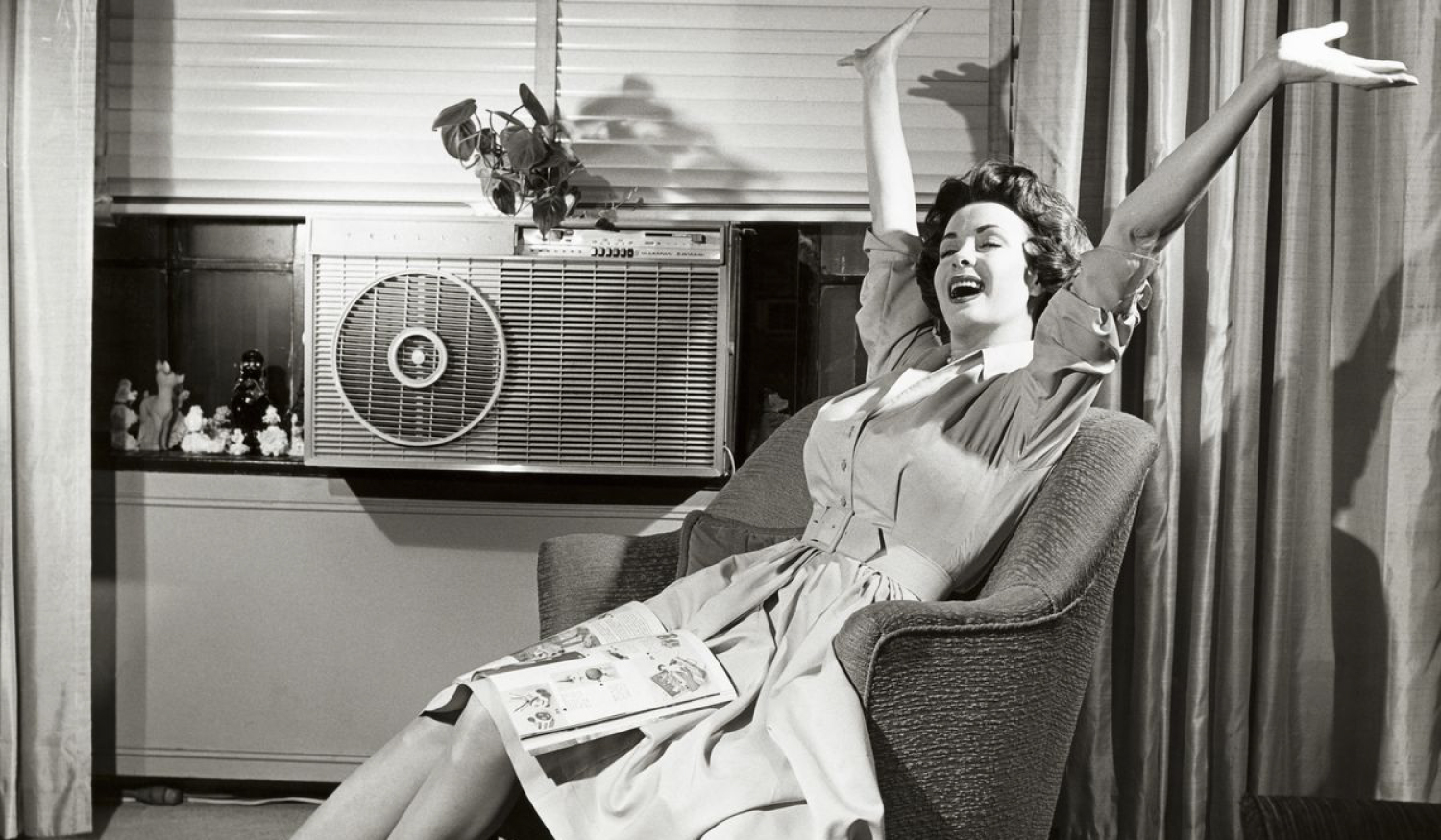 Photo of a woman enjoying window air conditioning in the 1950s.