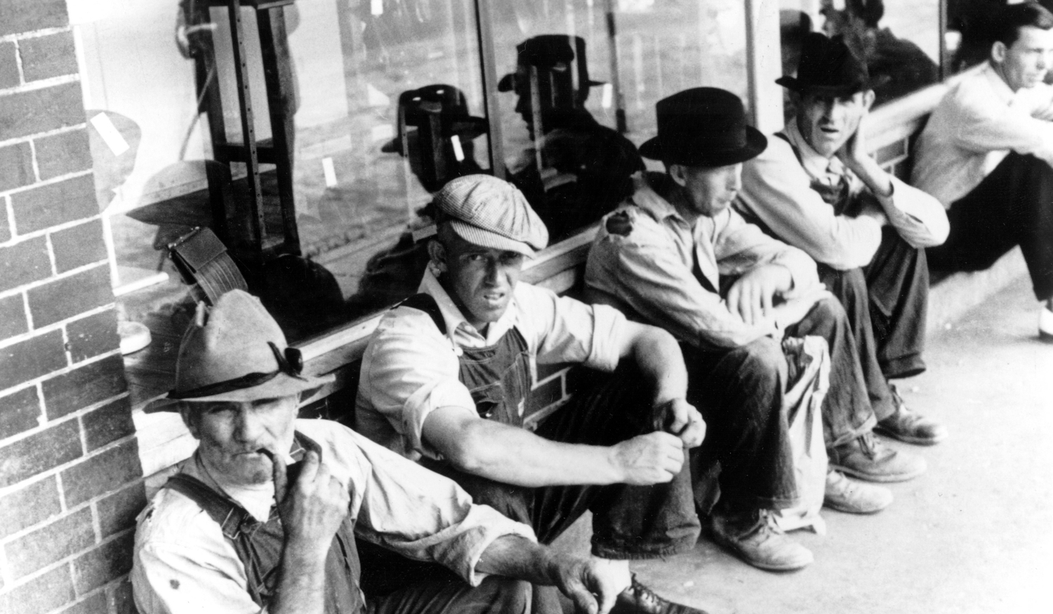 group of men sitting in front of store in the 1930s