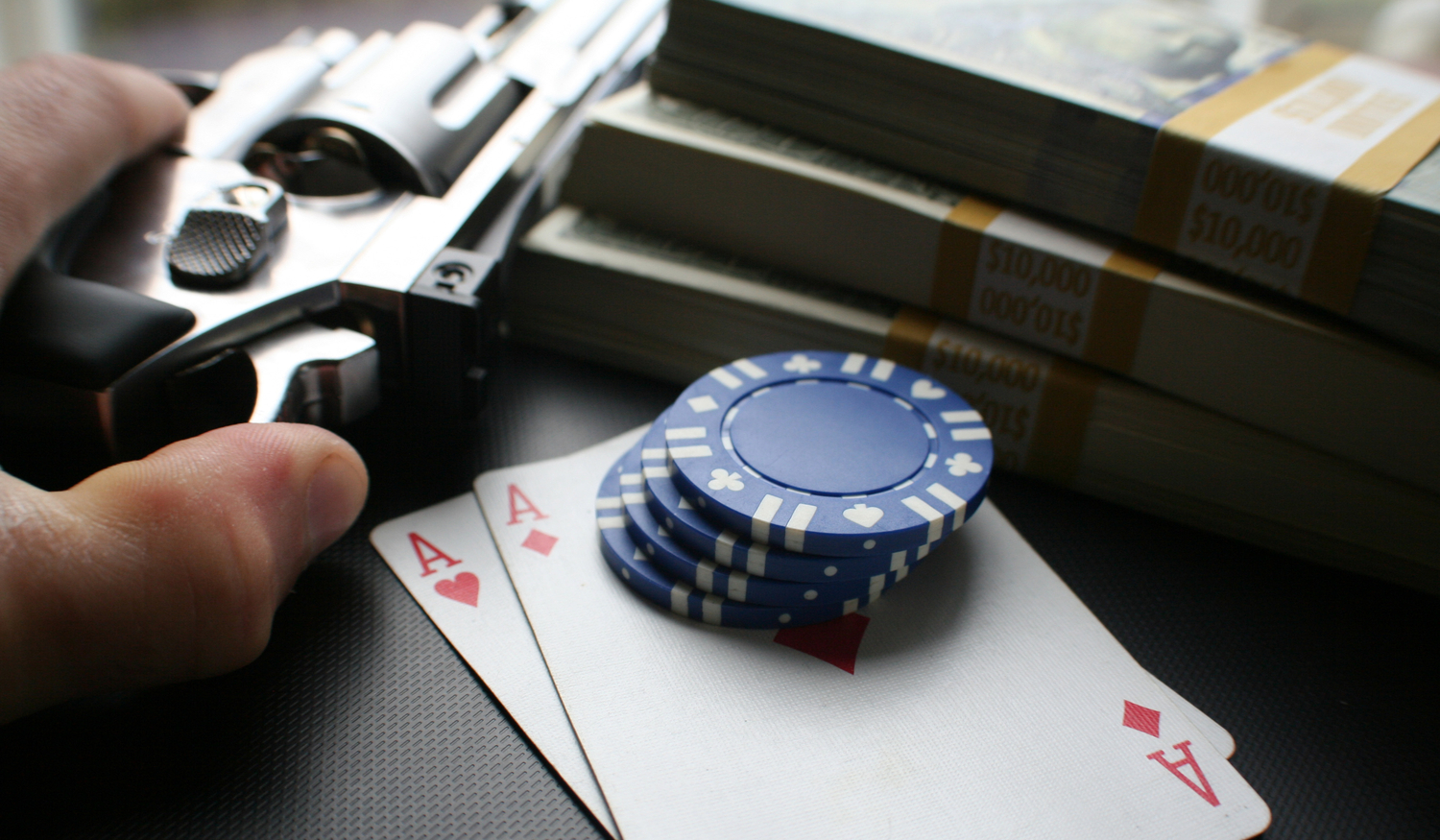 gun, stack of money, and poker chips and playing cards